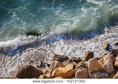 Beautiful large yellow stones in green waves on sea coast
