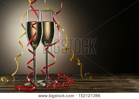 Two champagne glasses on table decorated yellow and red ribbons