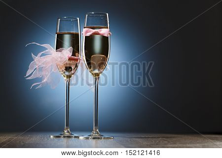 Champagne glasses with pink grooms bow-tie and brides veil