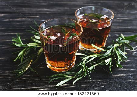 Cold Rosemary Tea With Ice On Wooden Table