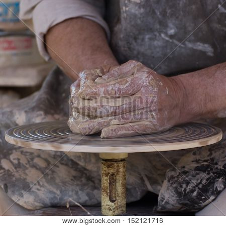closeup shot of artisan mans potters hands who sculpts pot on working spinning wheel circle
