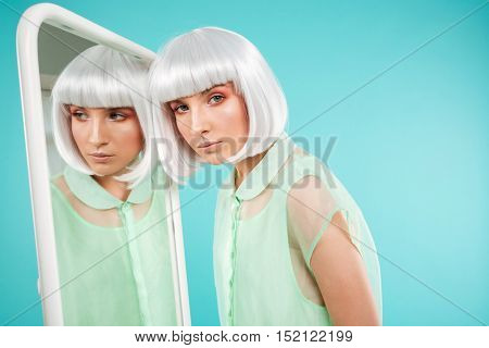 Portrait of stylish young woman in blonde wig near the mirrror