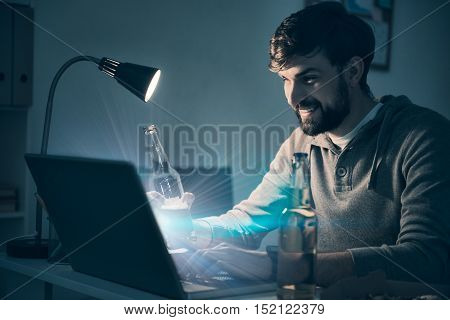 Enjoy the evening. Handsome young smiling man playing videogames and using the laptop while drinking beer.
