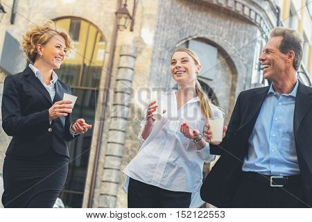 Happy man and women are resting after work. They are walking on street and drinking coffee. Businesspeople are communicating and laughing