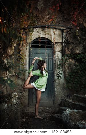 young woman in yoga balance position in front of old metal door and cliff autumn day