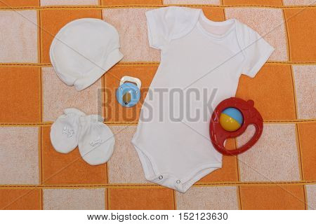 Clothing white set   bodysuit ,  cap ,  booties, a pacifier and toy strawberry. Clothes for baby close up. Things for babies in orange and white plaid.