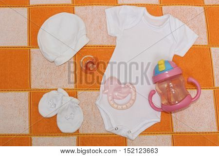 Clothing set white bodysuit , cap , booties,pink nipple , a duck teether and feeding Cup. Clothes for baby close up. Things for babies in orange and white plaid .