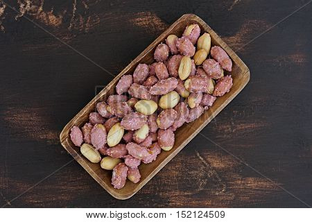 Salty roasted peanuts on bamboo plate, top view