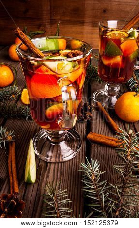 Christmas mulled wine with the addition of fragrant spices, apples, mandarins and oranges. With Christmas tree branches and pine cones