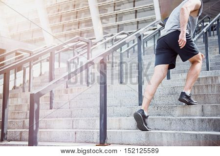 Stairway to health. Young active enthusiastic man climbing up the stairs of a stadium wearing sportswear before having his training.