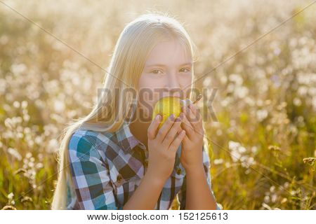 Cute little girl or teenager eaten healthy and juicy pear outdoor.