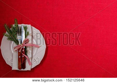 The plate is empty. Napkin. A sprig of Holly. Cutlery. A festive table setting. Christmas. Christmas decorations. The red background. The view from the top. Place for text.