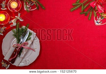 The plate is empty. Napkin. A sprig of Holly. Candles. Cutlery. A festive table setting. Christmas. Christmas decorations. The red background. The view from the top. Place for text.