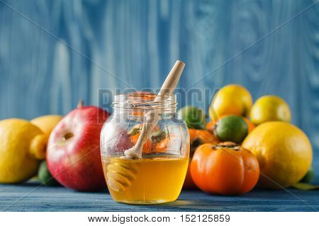 Apple And Honey On Wooden Table Over Blue Background