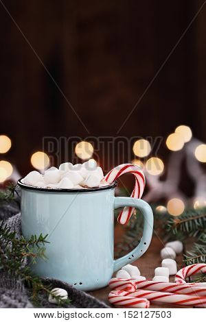 Enamel cup of hot cocoa with mini marshmallows and candy canes with pine boughs and gray scarf against a rustic background with beautiful Christmas lights of bokeh. Could also be coffee.