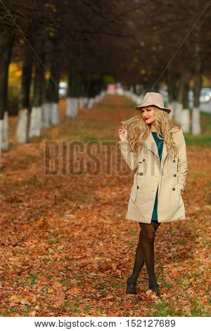 Beautiful elegant woman standing full length in fashionable beige hat in a park in autumn. free space. concept autumn
