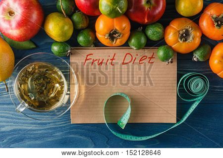 Concept Of Diet. Low-calorie Fruit Diet. Diet For Weight Loss. Plate With Measuring Tape And Fruits