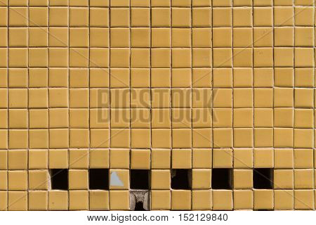 A wall surface with small yellow tiles and holes