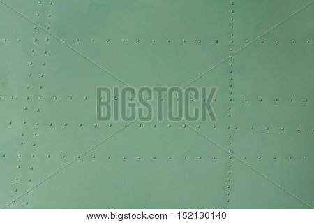 Old painted metal background detail of a military aircraft surface corrosion metal texture with rivets.
