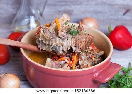 braised pork bone in pan on a wooden background