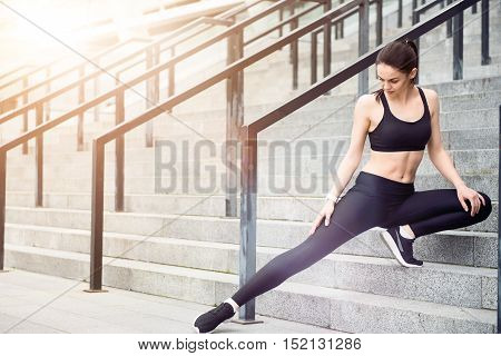 Love your body. Active young concentrated girl appending time on stadium and doing her exercises wearing sportswear.
