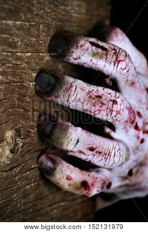 closeup of a scary and bloody hand scratching a rustic wooden surface with his rotten fingernails