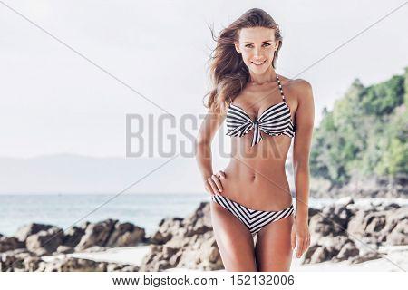 Woman in bikini walking on tropical beach