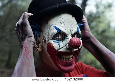 closeup of a scary evil clown in the woods smiling while is adjusting his bowler hat