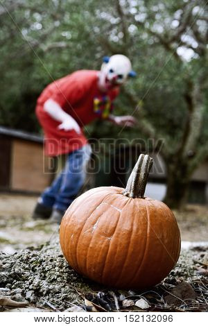closeup of a pumpkin outdoors and a scary evil clown in the background