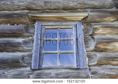 Small Old window with glass with a blue sky on the background of the wooden wall of the countryside log house.