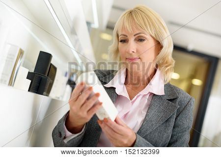 Confident middle-aged woman is buying cosmetics in boutique. She is holding cream box and reading label with interest