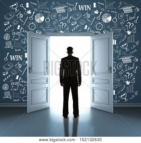 Back view of young businessman standing in room with business icons on wall against open door with bright light. Success concept