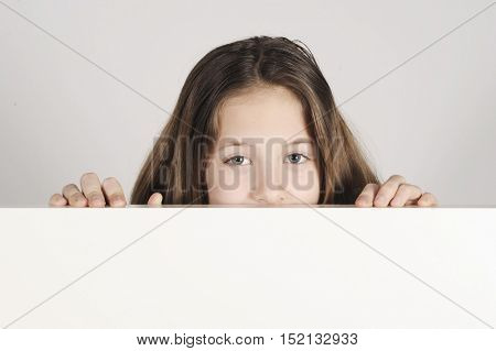 Image of a teenager girl looking up from behind a wall, isolated on white background.