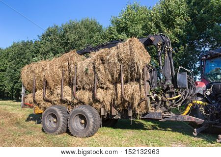 Agricultural tractor with trailer filled with round hay bales in autumn