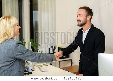 Successful purchasing. Happy businesswoman and shop assistant are shaking hands. They are standing and smiling in office