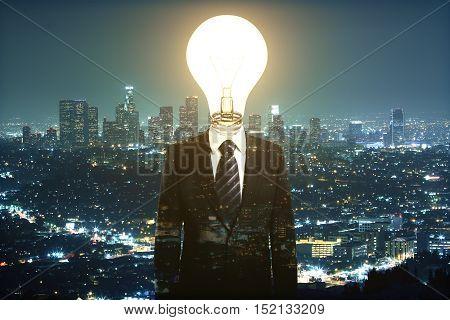 Abstract light bulb headed businessman on night city background. Idea concept. Multiexposure