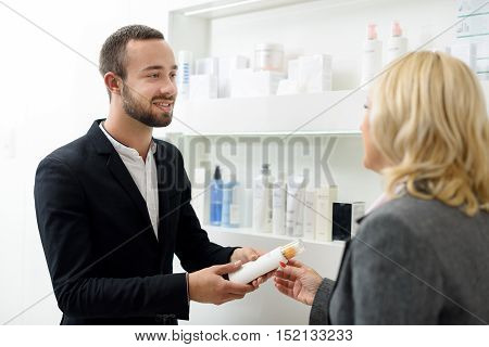 Confident male shop assistant is advising cosmetic product to woman. She is standing near shelves and smiling