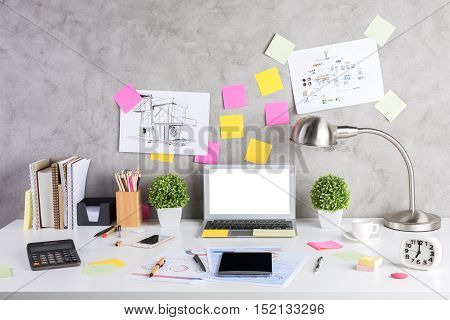 Close up of creative designer desktop with electronic devices decorative plants calculator colorful supplies and other items. Mock up
