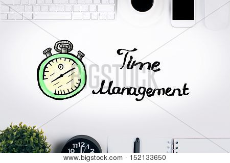 Top view of white desktop with electronic devices decorative plant supplies and creative clock sketch. Time management concept