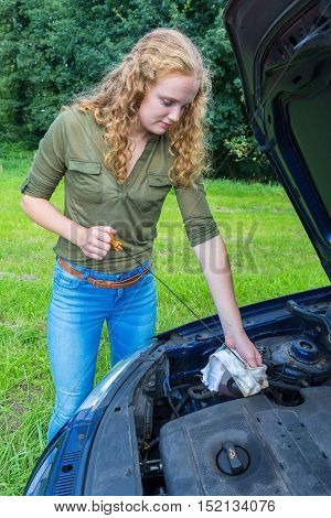 Dutch woman investigates car oil level with dipstick