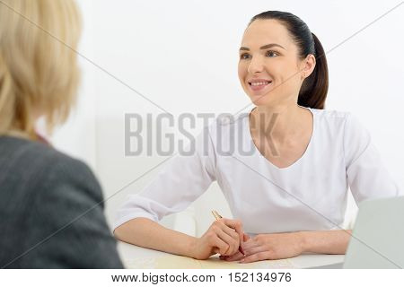 Female doctor is writing prescription for patient. She is sitting at desk and smiling