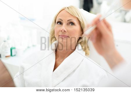 Mature woman is visiting beautician at clinic. She is sitting and looking at doctor with trust