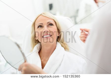 Cheerful mature woman is getting skincare treatment at beauty salon. She is sitting in bathrobe and smiling. Cosmetologist is holding mirror and pencil