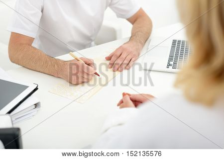 Close up of male doctor hands writing prescription for woman. He is sitting at desk in office