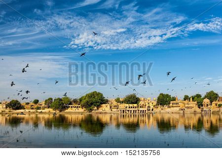 Indian tourist landmark Gadi Sagar - artificial lake with pigeons in the sky. Jaisalmer, Rajasthan, India