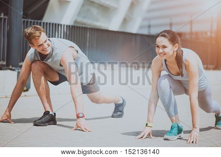 Couple working out. Beautiful slim woman and a handsome joyful man smiling and standing in sprint start position while preparing to run outdoors.