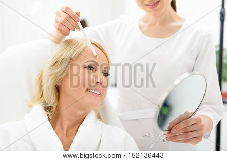 I like my skin. Joyful mature woman is sitting at beautician office and smiling. She is looking at mirror with excitement. Cosmetologist is touching her forehead with white pencil