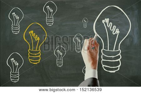 Hand drawing light bulbs on chalkboard. Ideas concept