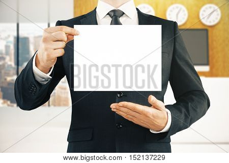 Close up of businessperson in suit holding empty paper sheet in modern office interior. Mock up. Presentation concept