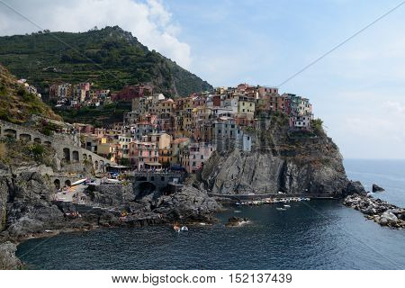 Manarola Italy - September 4 2016: Small bay and port in Manarola city in Liguria Italy. One of five Cinque Terre cities (unesco world heritage). Unidentified people visible.